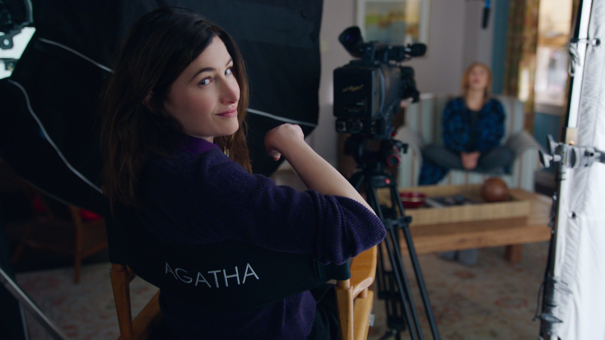 Agatha Harkness (Kathryn Hahn) sits in a director's chair and turns to camera smiling in 'WandaVision'