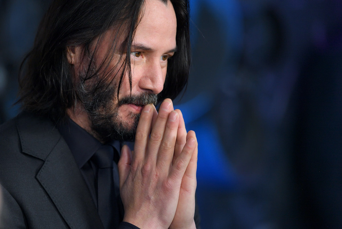 Keanu Reeves wears black and holds his hands to his lips