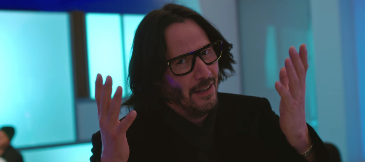 Keanu Reeves wears glasses and holds his arms up in 'Always Be My Maybe'
