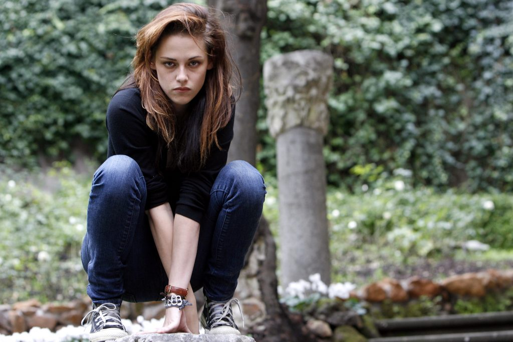 Twilight star Kristen Stewart poses for cast photos while crouching in blue jeans