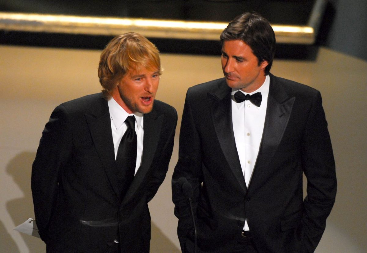 L-R: Owen Wilson and Luke Wilson in suits with Owen speaking into a microphone
