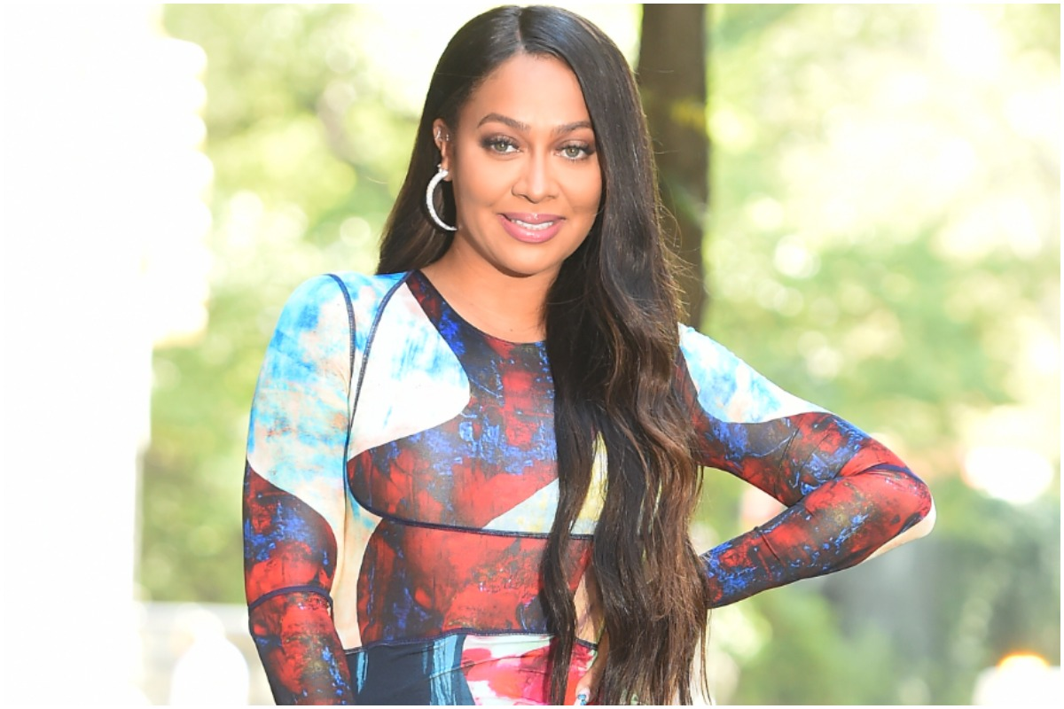 La La Anthony smiling with her hand on her hip at an event.
