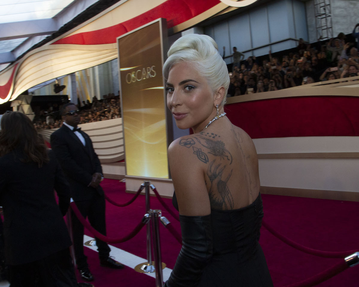 Lady Gaga turns and smiles in a black dress at the Oscars