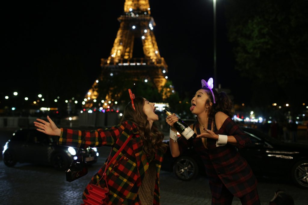 Lily Collins and Ashley Park on the set of 'Emily in Paris' drinking champagne in front of the Eiffel Tower