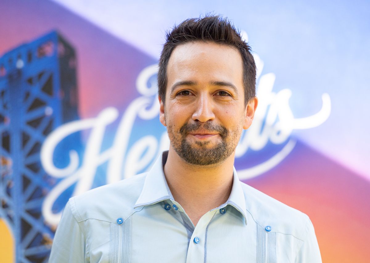 Lin-Manuel Miranda smiles and poses in front of a display of 'In The Heights'