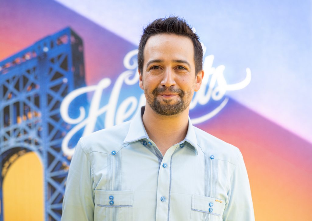 Lin-Manuel Miranda smiles in blue clothes in front of the 'In The Heights' poster