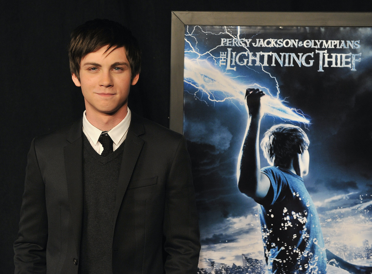 Logan Lerman wears a black suit and tie at the premiere of 'Percy Jackson and The Olympians: The Lightning Thief' in 2010. He stands in front of a blue and white poster for the film, which shows him holding a lightning bolt.