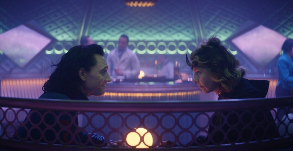 Tom Hiddleston as Loki wearing a blue jumpsuit and sitting across from Sophia Di Martino, who plays Sylvie. She wears a green and gold and black uniform and brass headband with a horn. They sit at a table in a room with purple and blue lights.