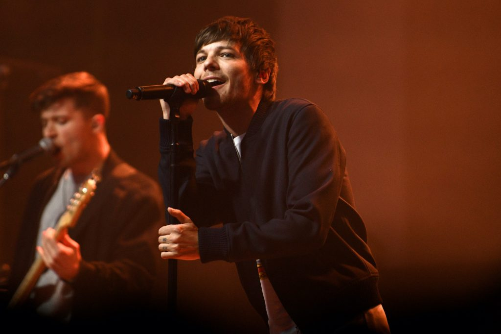 Louis Tomlinson singing into a microphone