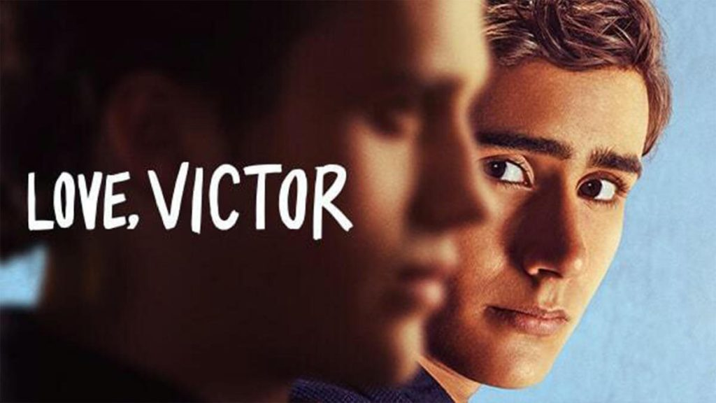 Victor (Michael Cimino) looks at Benji (George Sear) in cover art for 'Love, Victor.' Sear is in the front out of focus, and Cimino stands behind him in focus in front of a light blue background. White text that reads 'Love, Victor' goes across the left side of the photo.