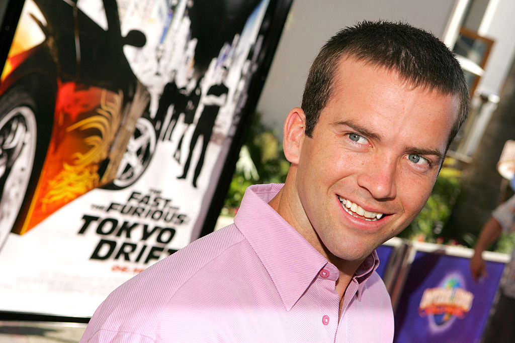 Lucas Black wears a pink shirt with a smile while walking the red carpet at 'The Fast and the Furious: Tokyo Drift premiere.