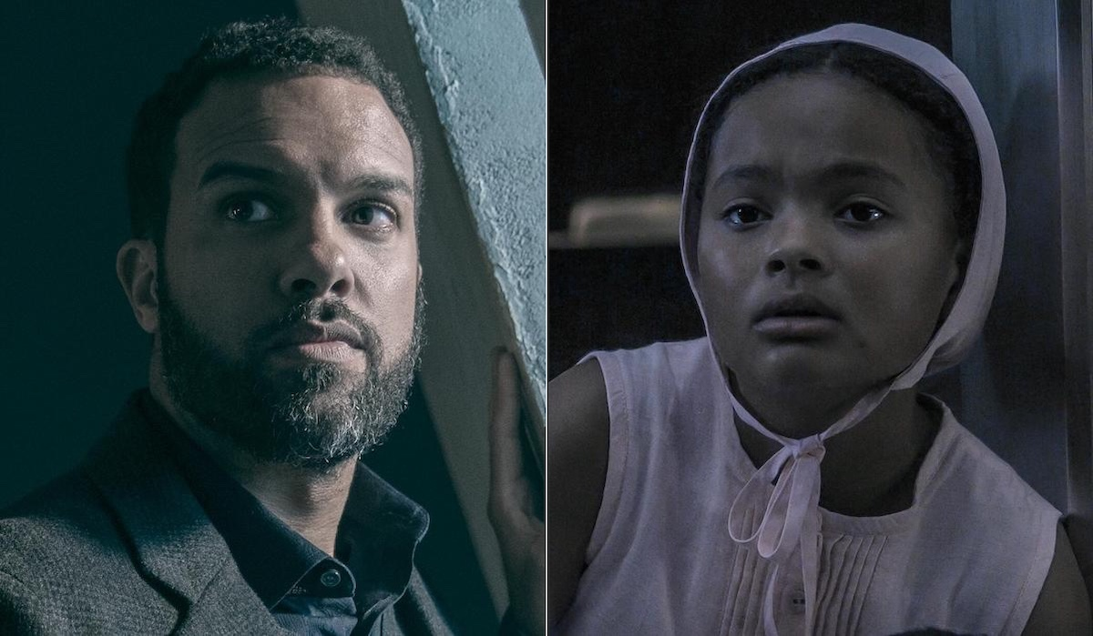 O-T Fagbenle as Luke (L) and Jordana Blake as Hannah (R) in 'The Handmaid's Tale' Season 4. He wears a sweater and tweed suit and stands near a window. She wears a pink dress and pink bonnet while holding a doll in a large glass cell.