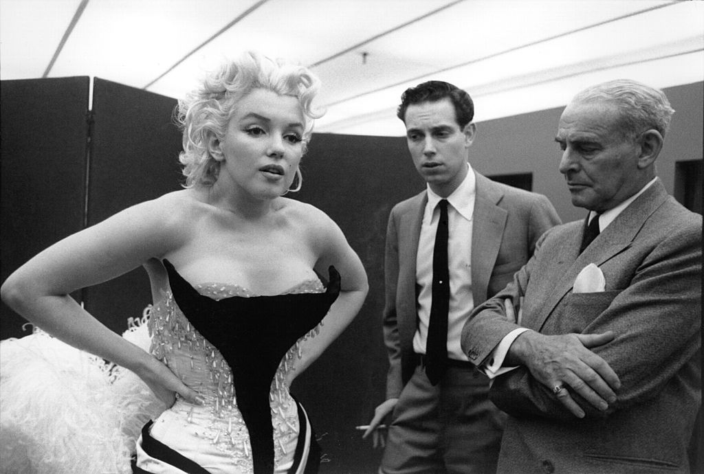 Marilyn Monroe is being fitted for a costume while two men look on.
