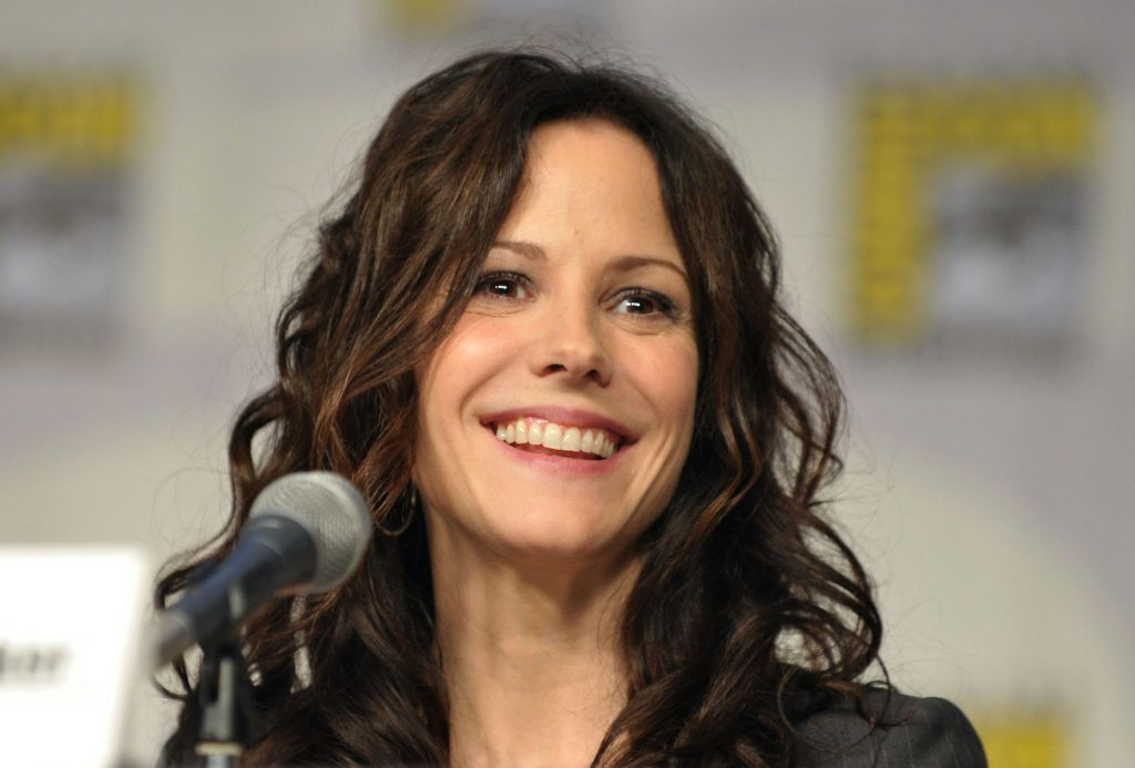 Mary-Louise Parker smiling, seated behind a microphone