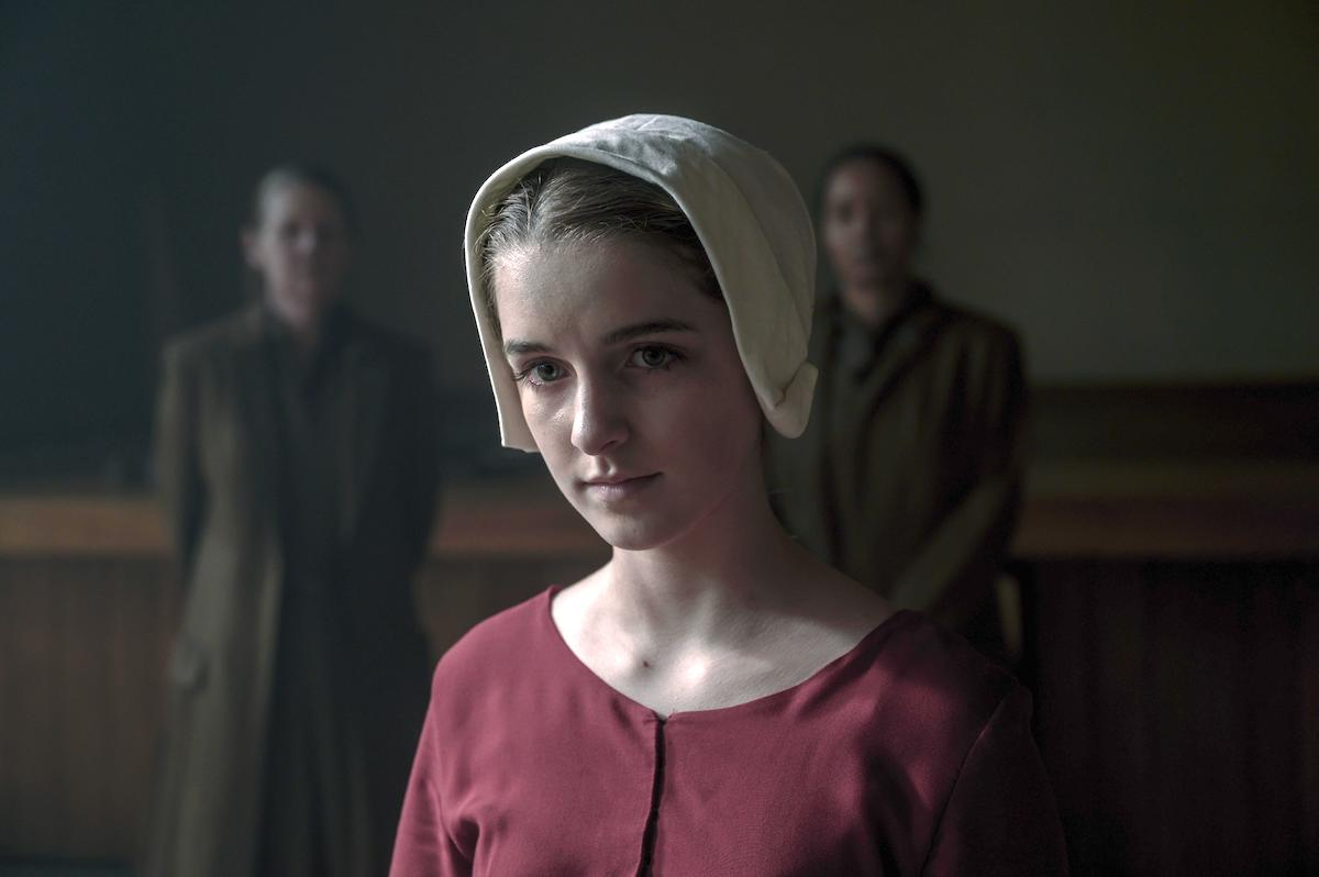 McKenna Grace dressed in a red Handmaid dress and white bonnet as Esther Keyes in 'The Handmaid's Tale' Season 4. Two Aunts dressed in brown dresses and coats stand behind her.
