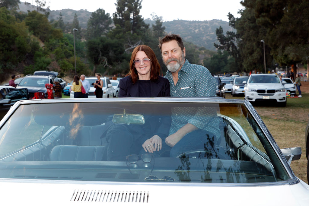 Megan Mullally and Nick Offerman sit on top of their convertible's seats as they prepare to watch a drive-in movie. Offerman has his are around Mullally and they're all smiles.