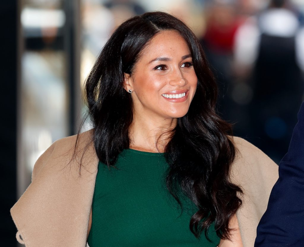 Meghan, Duchess of Sussex grins in a green dress and beige coat