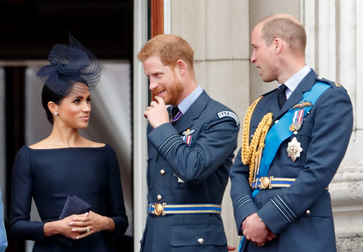 Meghan Markle, Prince Harry, and Prince William, standing on the balcony of Buckingham Palace for a flypast in 2018