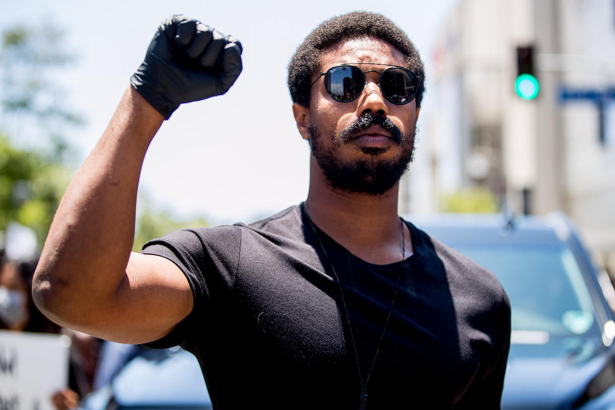 The Wire alum Michael B. Jordan wears black sunglasses, a black T-shirt, and. a black glove as he throws up a fist
