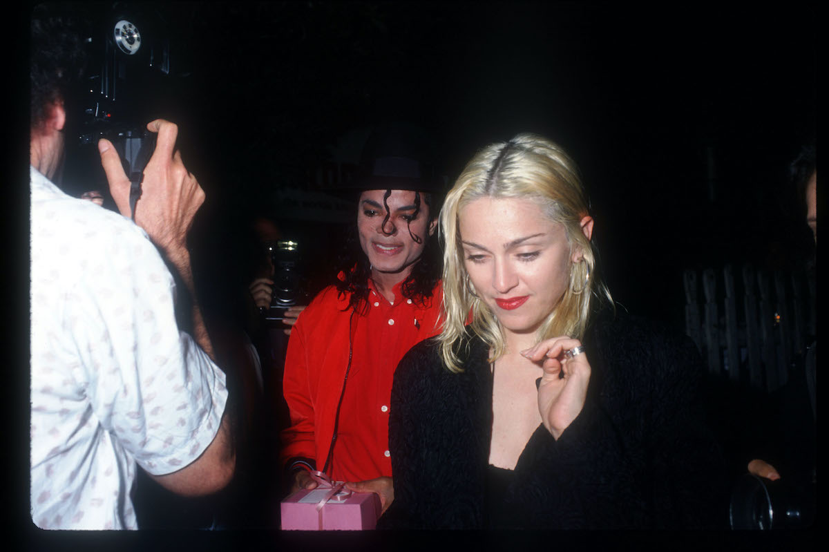 Michael Jackson -- wearing red clothes and a black hat -- and Madonna, wearing black, pass a photographer in 1991