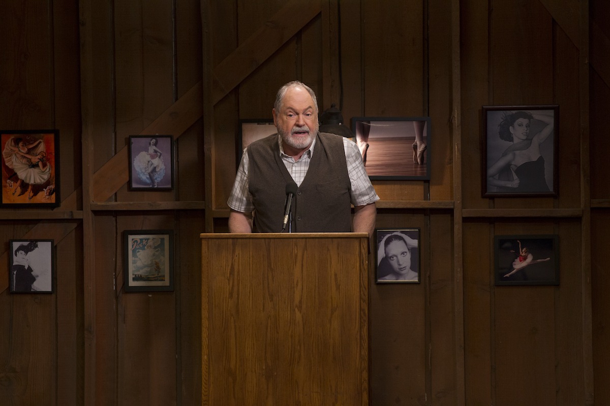 Michael Winters stands behind a podium on the set of 'Gilmore Girls: A Year in the Life'