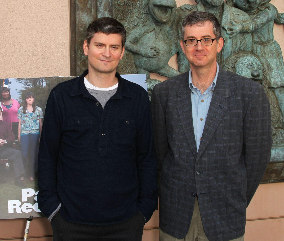 Mike Schur and Greg Daniels stand in front of a 'Parks and Recreation' sign at an Emmy screening