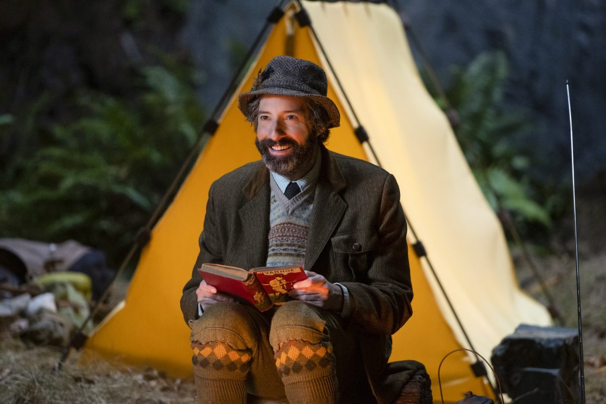 Mysterious Benedict Society: Mr. Benedict reads a book outside a tent