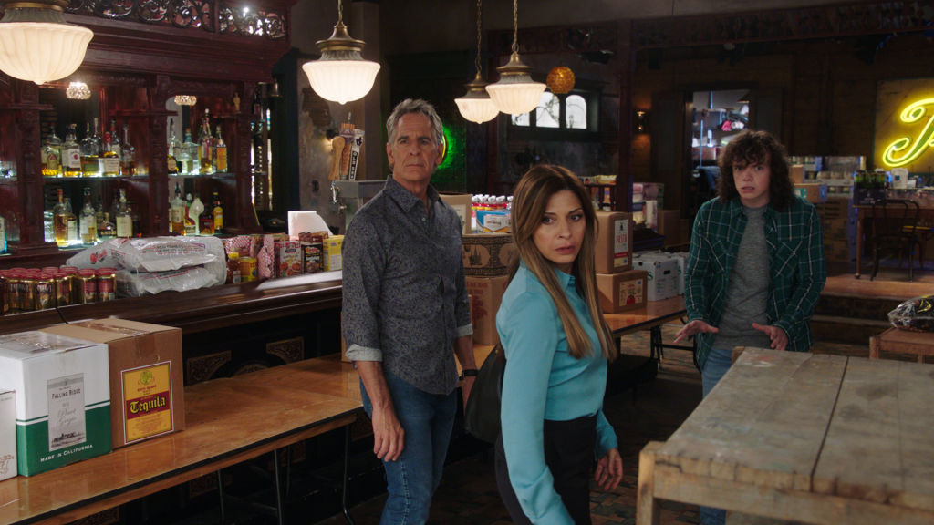 Scott Bakula as Special Agent Dwayne Pride, Callie Thorne as Sasha Broussard, and Drew Scheid as Connor Dean look concerned at Pride's bar.