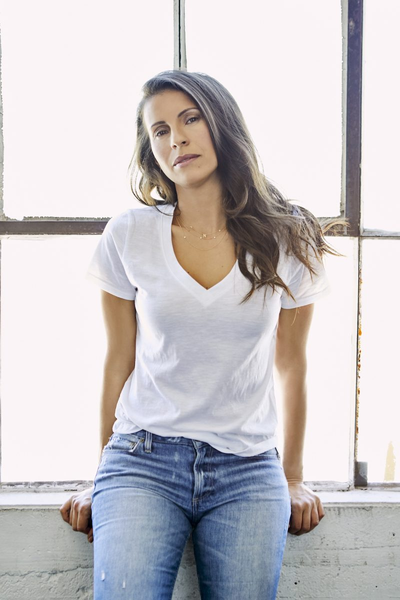 Natalia Castellanos wearing a white t-shirt in front of a window