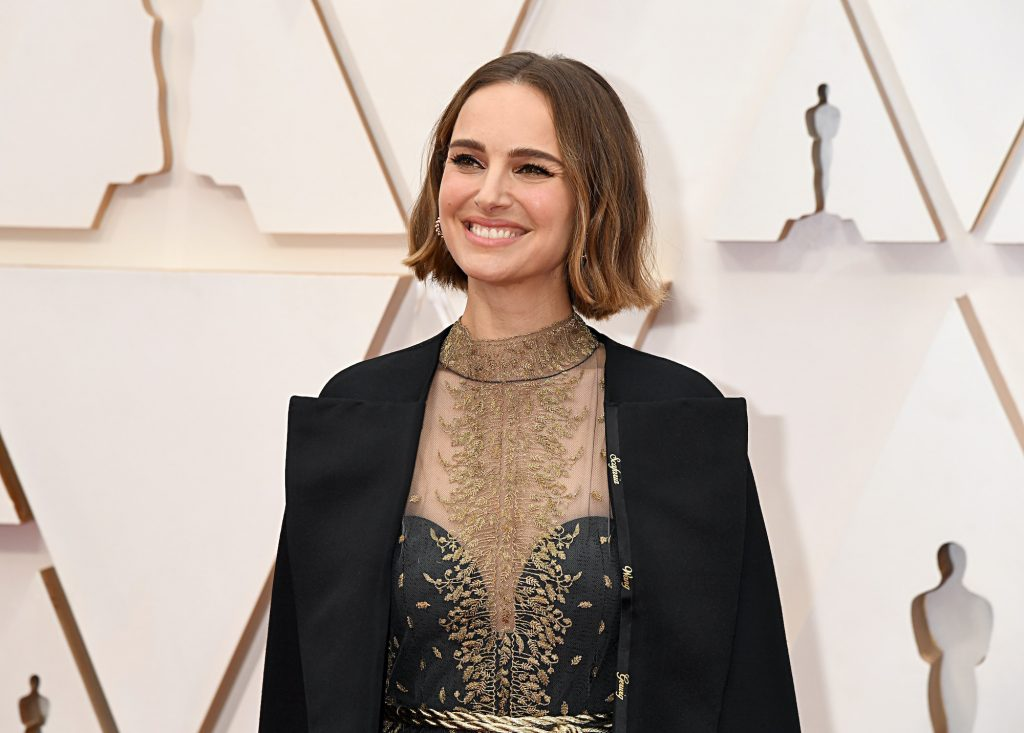 Natalie Portman smiling in front of a white background