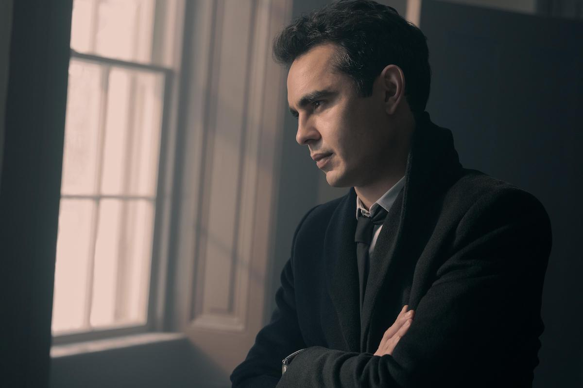 Max Minghella wears a black suit, black wool coat, and crossing his arms as he looks out a window as Nick in 'The Handmaid's Tale' Season 4 Episode 9, 'Progress'