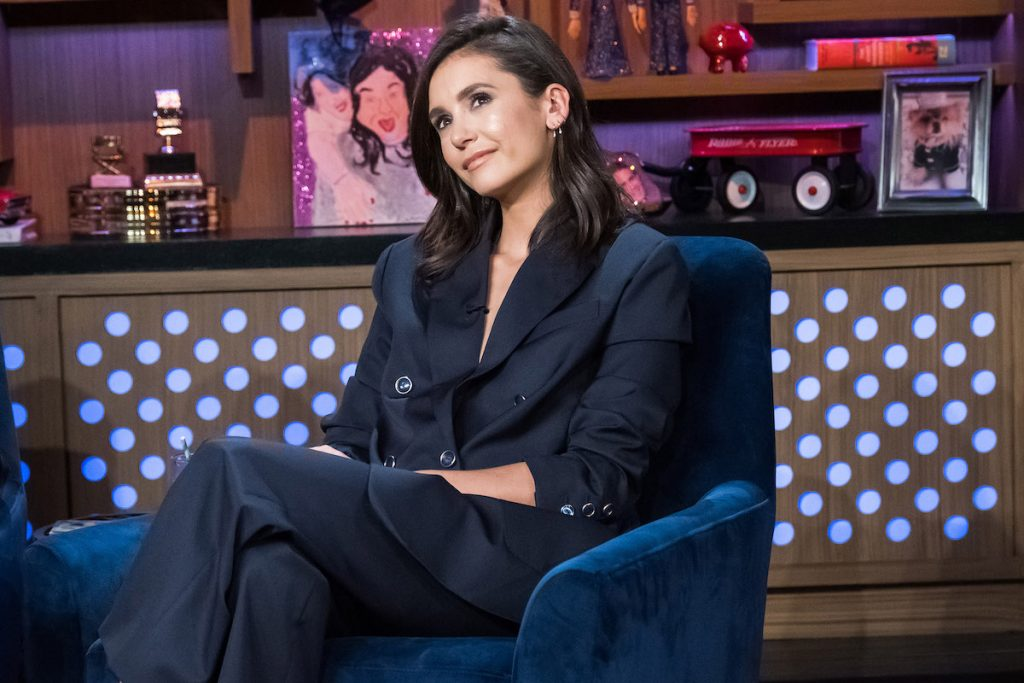 Nina Dobrev wears a suit as she sits in a chair.