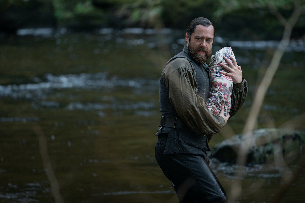 Richard Rankin as Roger in 'Outlander' Season 6 running by a river looking concerned and seemingly carrying a baby wrapped in a quilt