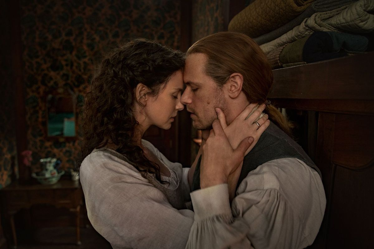 Caitriona Balfe and Sam Heughan embrace while wearing 1770s colonial clothing in 'Outlander' Season 6