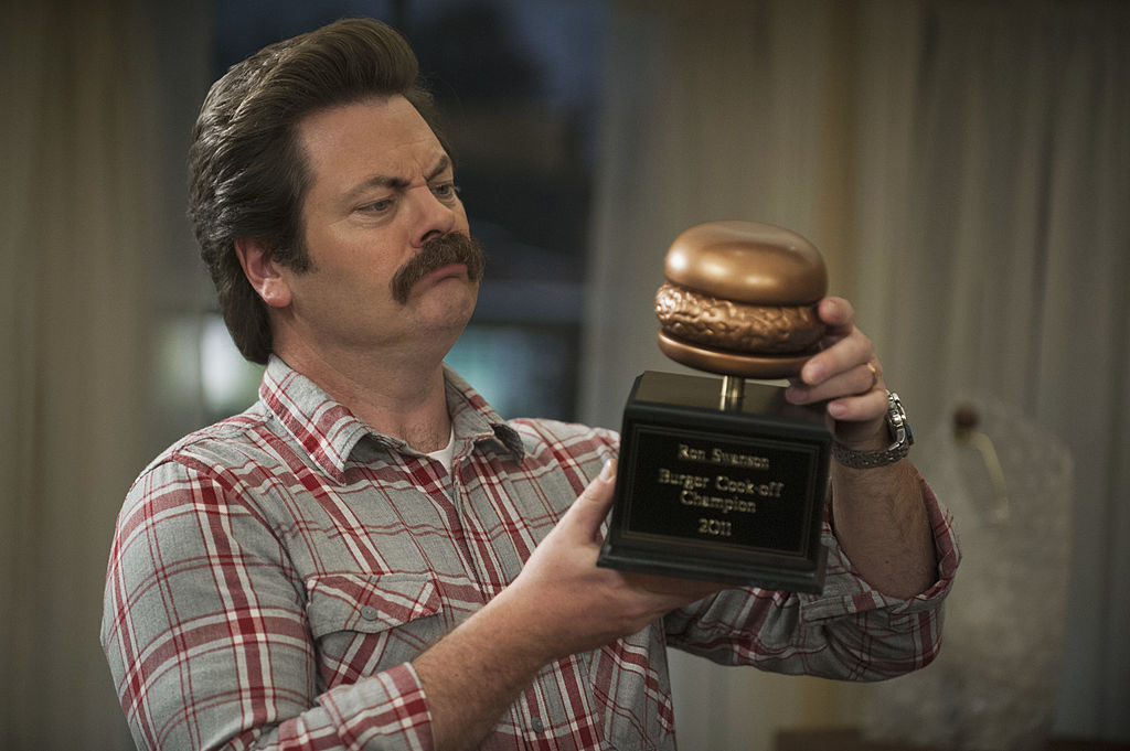 Nick Offerman as Ron Swanson in a plaid shirt holds a golden hamburger statue.