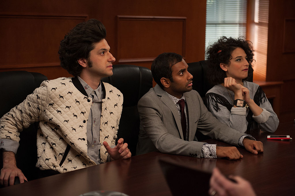 Ben Schwartz as Jean-Ralphio, Aziz Ansari as Tom Haverford, Jenny Slate as Mona Lisa sit at a table together looking at someone speaking who is out of frame.