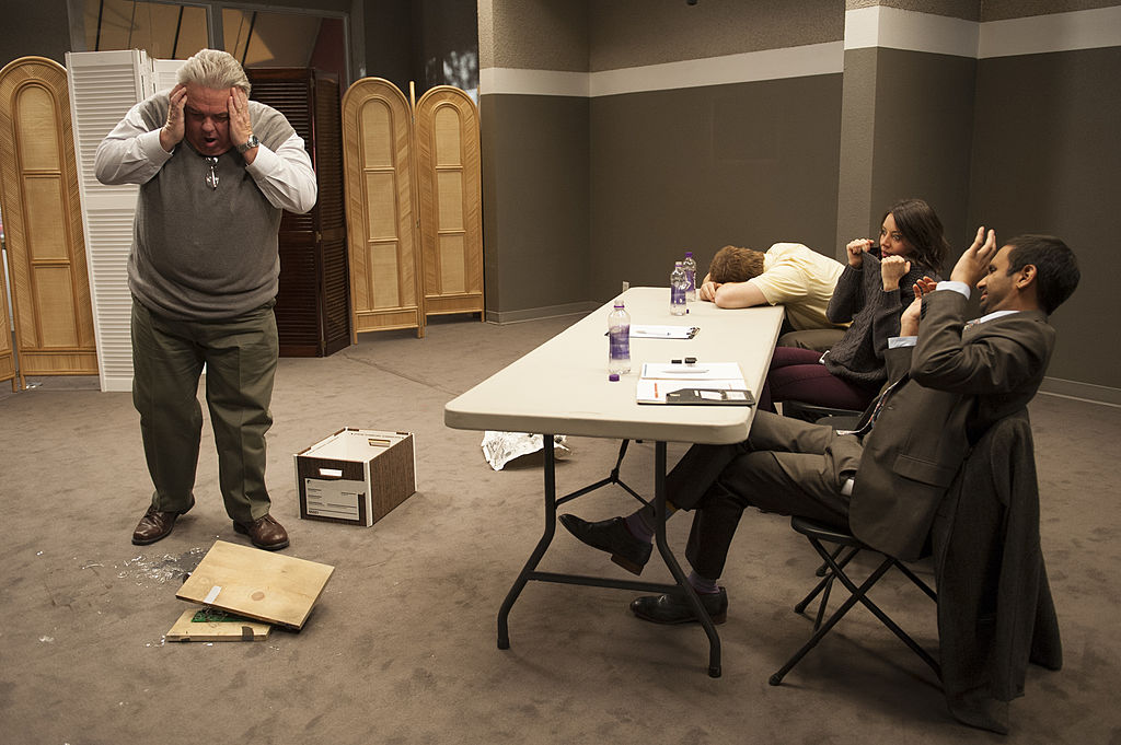 Chris Pratt as Andy Dwyer, Aubrey Plaza as April Ludgate, and Aziz Ansari as Tom Haverford watch Jim O'Heir as Jerry Gergich react after he drops a file box.