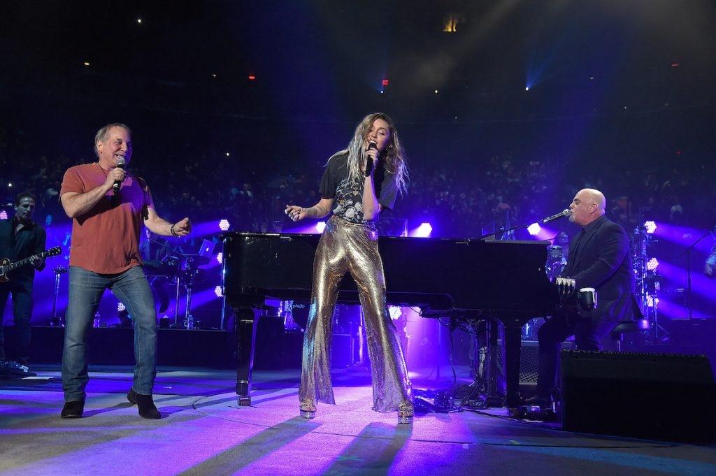 Paul Simon and Miley Cyrus sing as they stand near Billy Joel at the piano while performing at Madison Square Garden in 2017