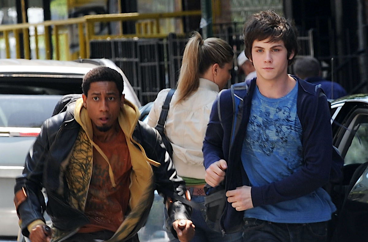 Logan Lerman dressed in a blue shirt and blue hoodie and jeans as Percy Jackson. He runs through a street in Brooklyn, New York with cast mate Brandon T. Jackson, who played Grover. Jackson wears an orange T-shirt, yellow zip-up hoodie, and black leather jacket.