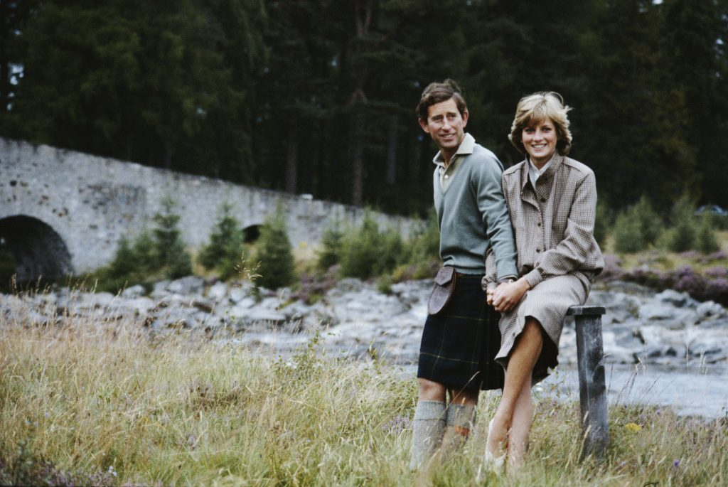 Prince Charles and Princess Diana smiling in front of a stream