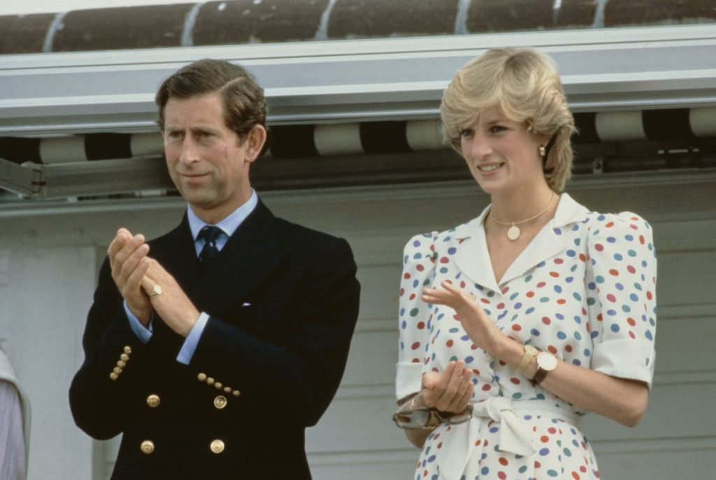 Prince Charles and Princess Diana clapping. The two had a lot of royal family scandals.