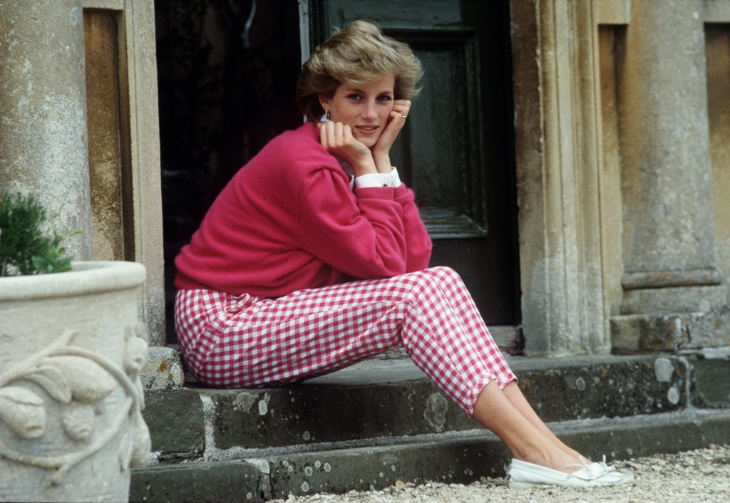 Princess Diana sitting on a step at Highgrove House in a pink sweater and checkered pants