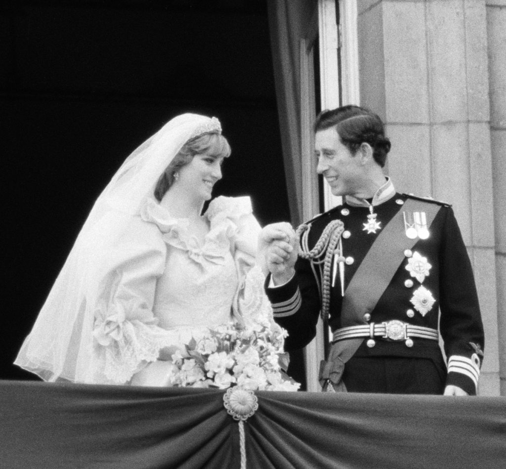 Princess Diana and Prince Charles holding hands and smiling on their wedding day