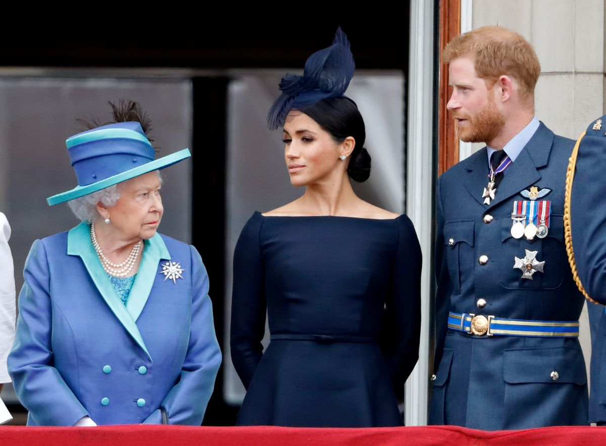 Queen Elizabeth II in a blue hat and suit, Meghan Markle in a navy dress and hat, and Prince Harry in military attire