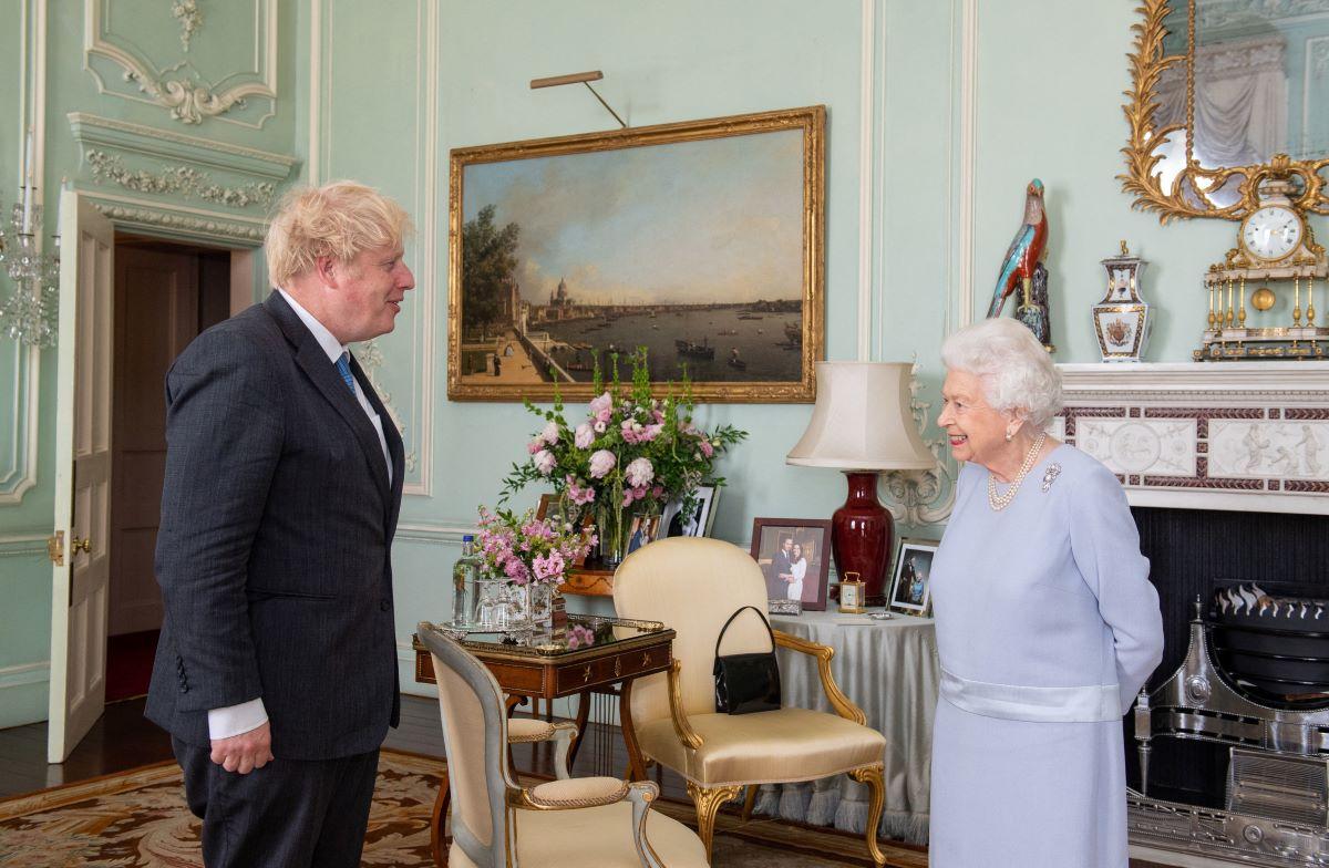 Queen Elizabeth II in a light blue dress and Boris Johnson in a dark suit