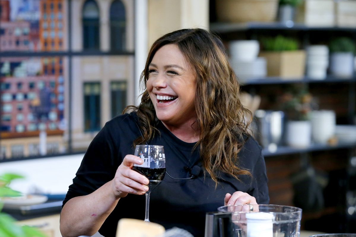 Rachael Ray smiling and holding a glass of wine