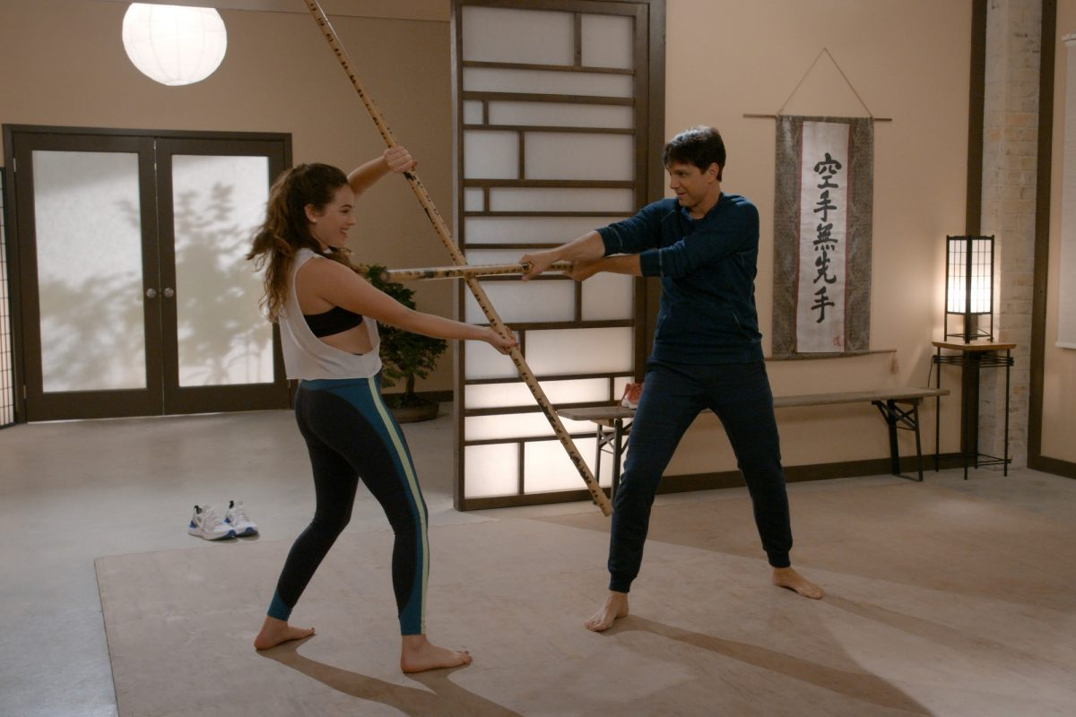 Ralph Macchio and Mary Mouser spar with staffs