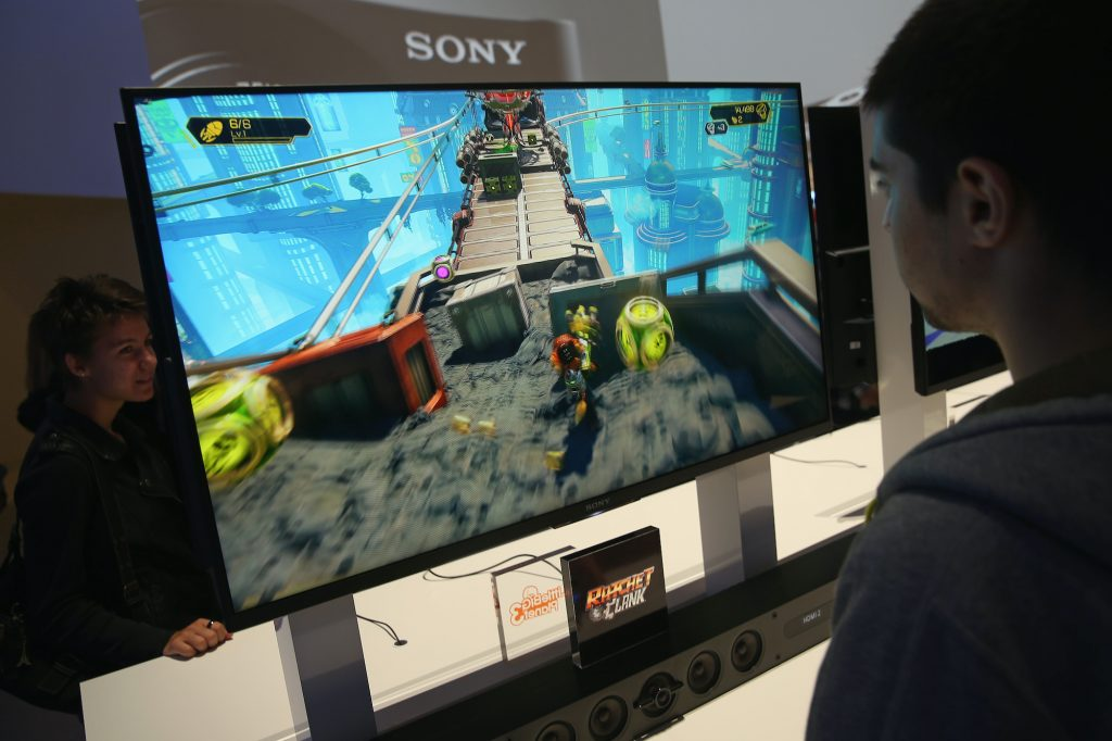 A fan plays the video game 'Ratchet and Clank' on a large computer monitor