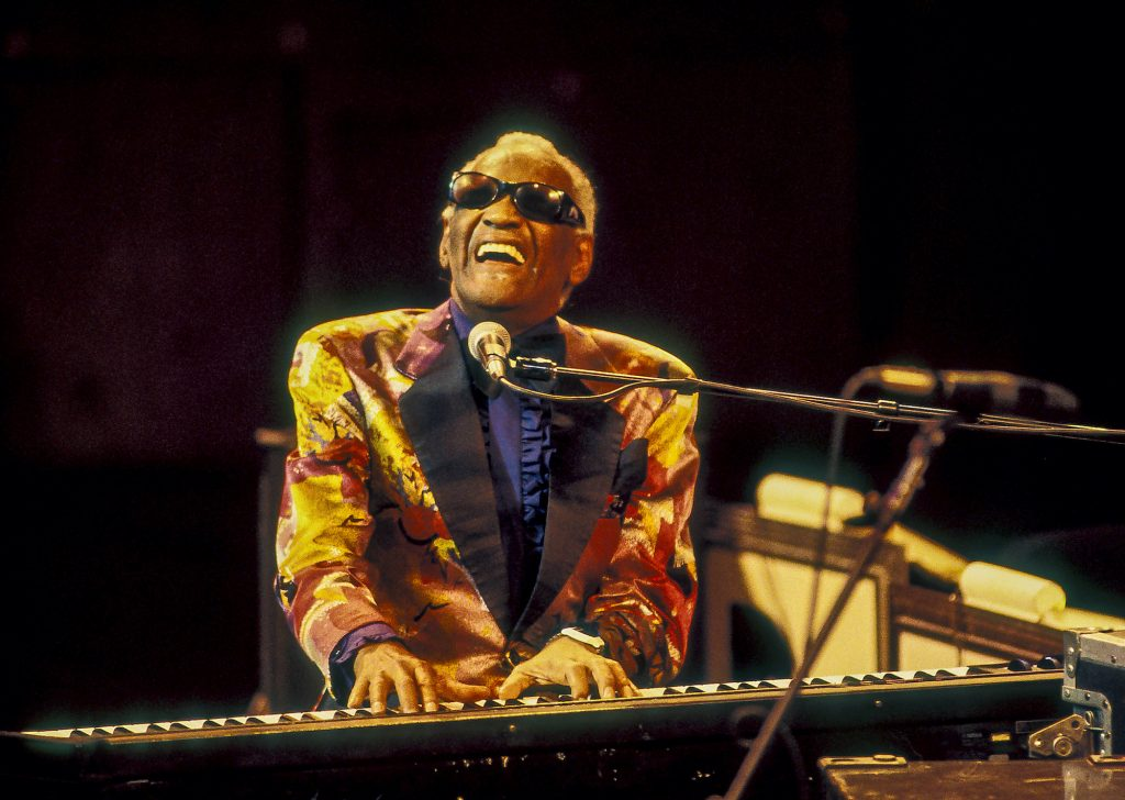 Ray Charles singing and playing on a keyboard