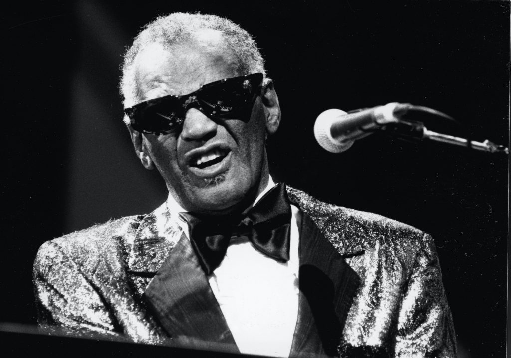 Ray Charles playing piano, singing into a microphone